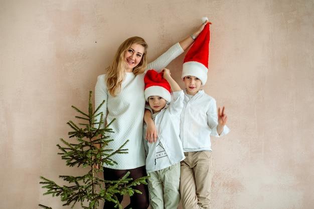 ピンクの壁とクリスマスツリーのそばにママと2人の息子。ミニマリズム。