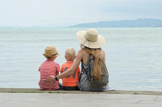 Мама и двое сыновей сидят на пристани и любуются морем и горами вдалеке. вид сзади