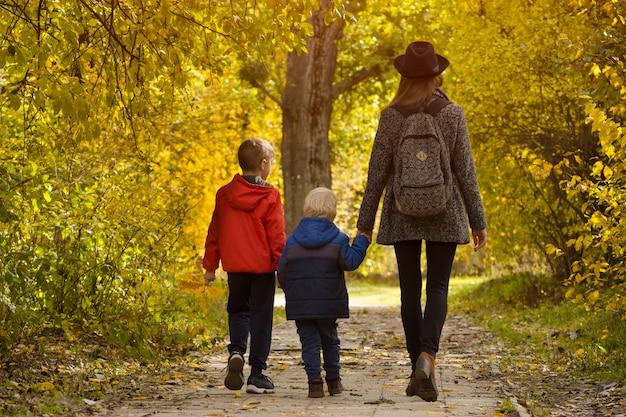 秋の森を歩くお母さんと2人の息子