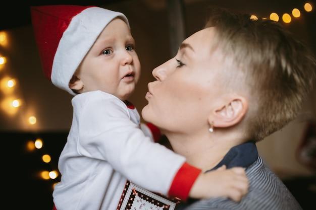 엄마와 크리스마스 모자에 화난 아기 소녀