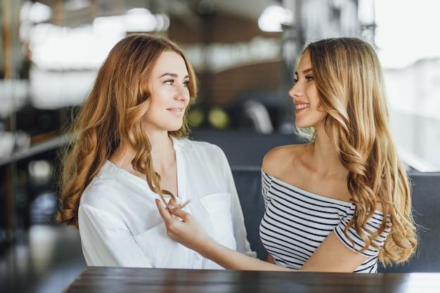 Мама и молодая красивая дочь-подросток смотрят друг на друга на летней террасе кафе в повседневной одежде.