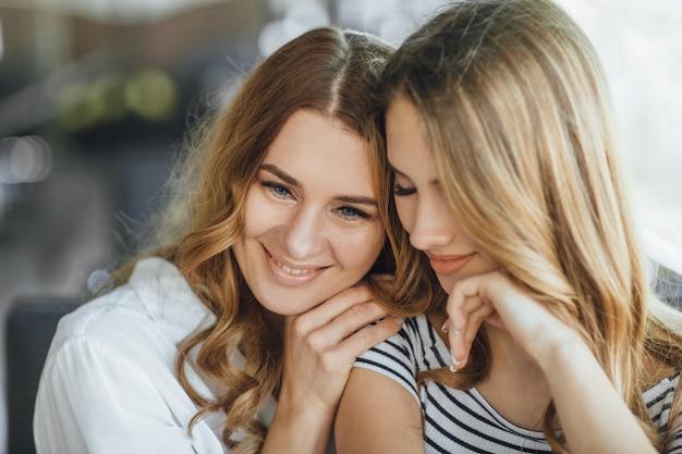 ママと若い美しい10代の娘がカジュアルな服装で夏のテラスカフェに抱擁