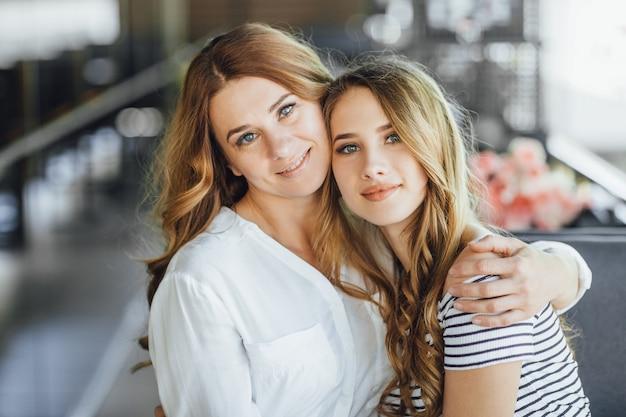 엄마와 젊고 아름다운 10대 딸이 캐주얼한 옷을 입고 여름 테라스 카페에서 포옹