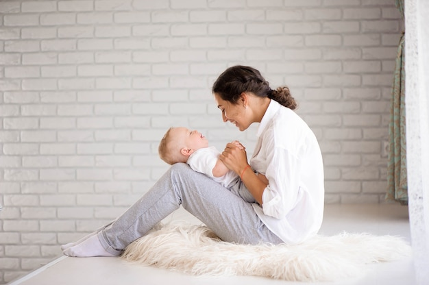 Mom and baby boy in diaper playing in sunny bedroom. family having fun together.