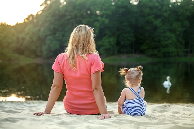 Mom and baby daughter sit and watch the lake. the concept of childhood, leisure and lifestyle.