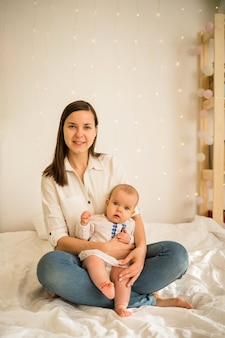Mom and baby daughter sitting on white blanket on the bed
