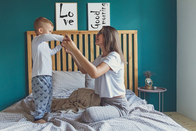 Mom and baby have fun and jump in the bedroom on the bed