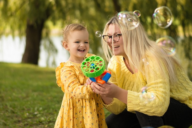 Mom and baby making soap bubbles, spring warm day, summer in the park