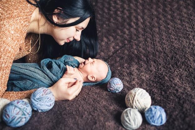 ママは生まれたばかりの赤ちゃんにかがみ、彼に微笑んだ。