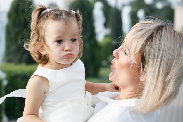 晴れた夏の公園で小さな娘を抱いて金髪のお母さん