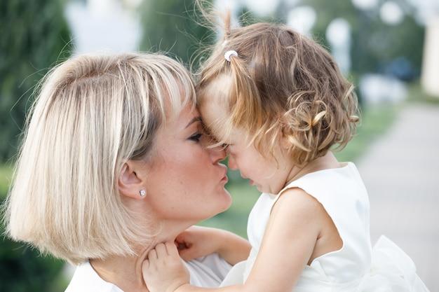 夏に公園で小さな娘を抱いて金髪ママ