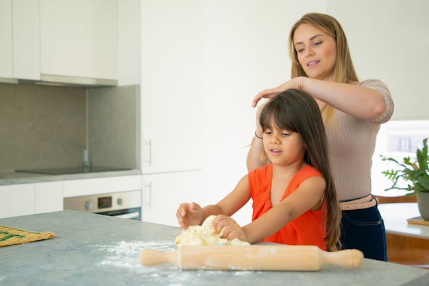 여자가 부엌 카운터에서 반죽을 만드는 동안 엄마 꼬기 딸 긴 머리. 엄마와 아이가 함께 베이킹. 가족 요리 개념