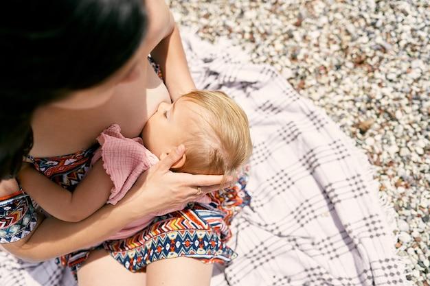 엄마는 자갈 해변 평면도 근접 촬영에 어린 소녀를 모유 수유