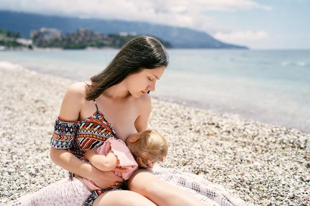 엄마는 자갈 해변에 앉아 어린 소녀를 모유 수유