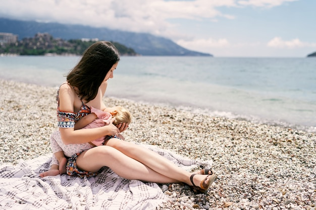 엄마는 자갈 해변에서 무릎을 꿇고 어린 소녀에게 모유 수유를 합니다.