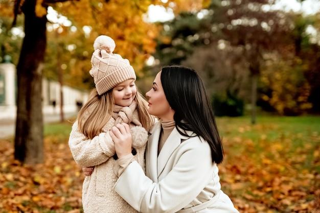 ベージュのキャップのママブルネットとブロンドの娘は手をつないで、秋の公園でお互いを見てください