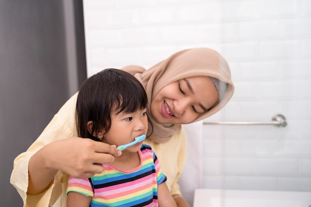 Mom brushes her kid's teeth