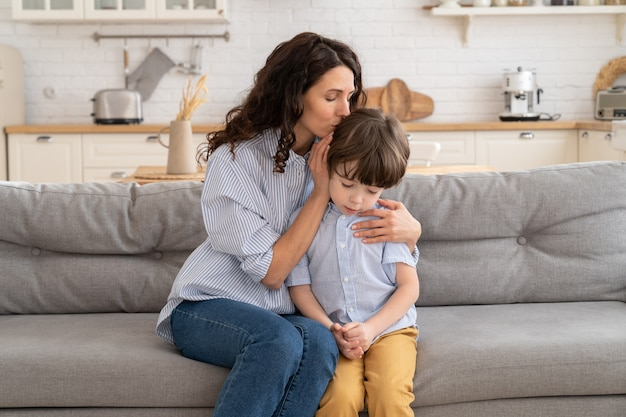 Mom calms frustrated preschool boy embracing and soothing