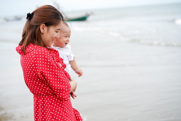Mom carry baby on the beach so happiness