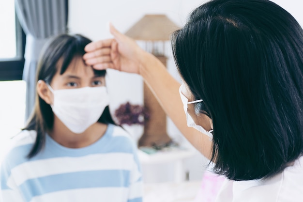 Mom checking her daugther temperature. they are under surgical face mask covering mouth and nose.