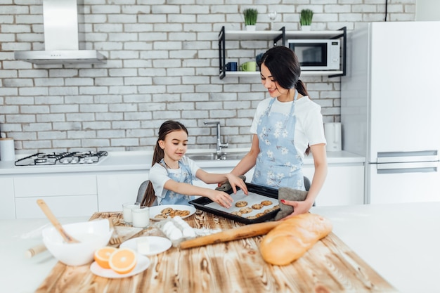 Mom and child cooking cookies together in modern white kitchen