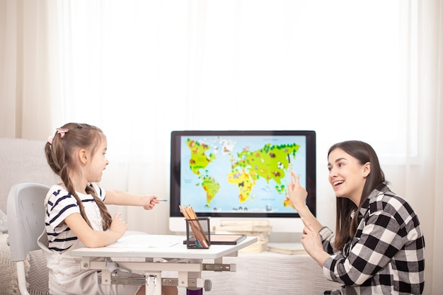 Mom and child do homework with geography using a map. home schooling and education concept.