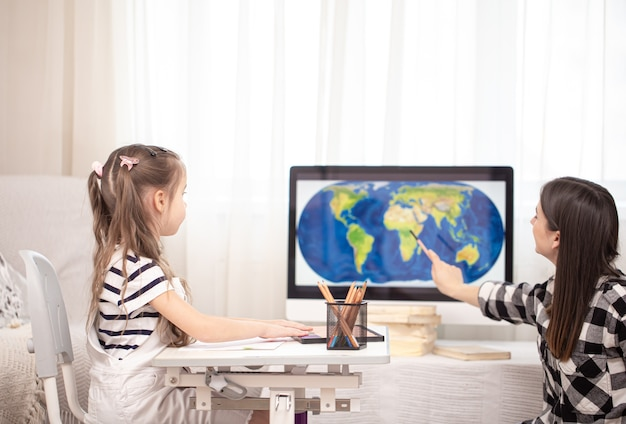 Mom and child do homework with geography using a map. home schooling and education