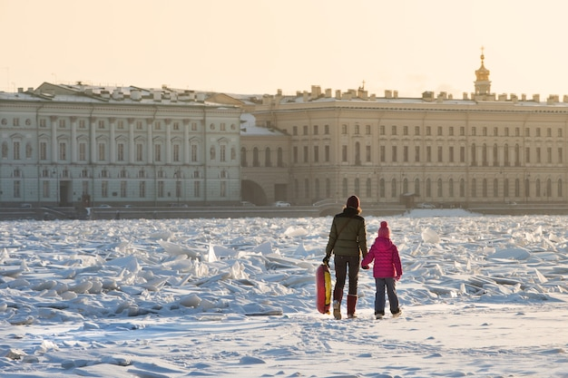 Mom and child walking on the ice of frozen river in sunny winter day, cityscape on background