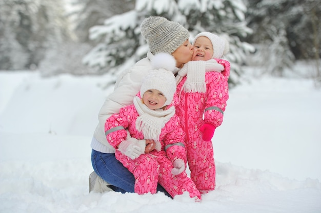Mom and children on a walk in the winter in the forest.