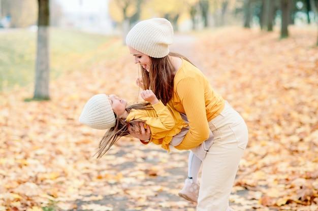 Мама кружит дочку на руках и развлекается в осеннем парке