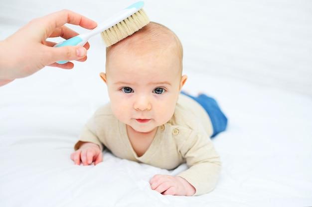 Мама расчесывает малыша специальной щеткой для волос на белом