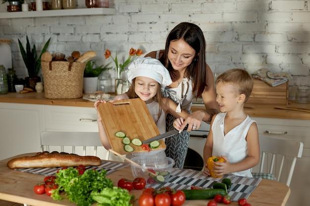 엄마는 아이들과 함께 점심을 요리합니다. 한 여자가 딸에게 아들에게서 요리하도록 가르치고 있습니다.