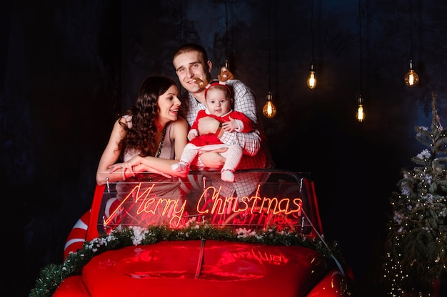 Мама, папа и девочка веселятся в рождественской ретро красной машине. родители с маленькой дочкой на рождественской фотосессии.