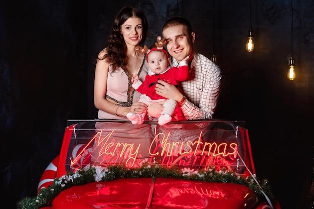 Мама, папа и девочка веселятся в рождественской ретро красной машине с рождественскими украшениями