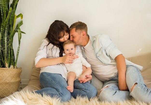 ベッドに座っているママ、パパ、女の赤ちゃん