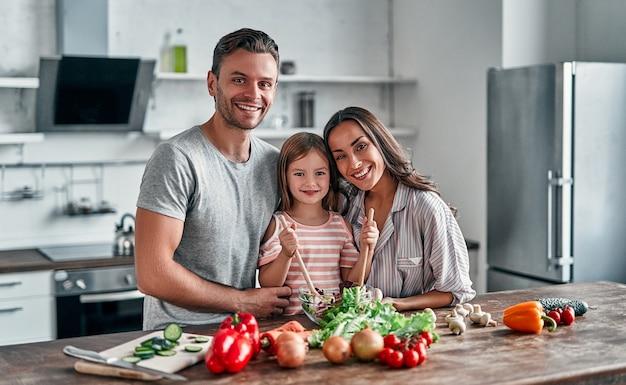 ママ、パパ、娘がキッチンで料理をしています。幸せな家族の概念。ハンサムな男性、魅力的な若い女性と彼らのかわいい小さな娘が一緒にサラダを作っています。健康的な生活様式。