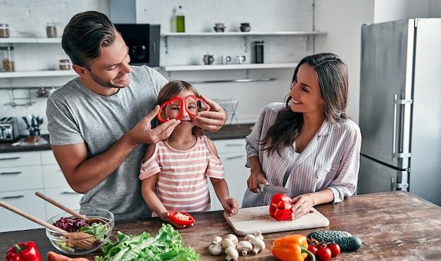Мама, папа и дочь готовят на кухне. концепция счастливой семьи. красивый мужчина, привлекательная молодая женщина и их милая маленькая дочь вместе делают салат. здоровый образ жизни.