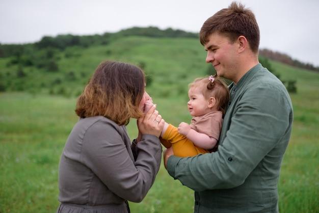ママ、パパ、娘。父は娘を抱きしめています。ママは小さな娘の足にキスします。