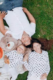 ママ、パパ、テディベアとピクニックに横たわっている娘。夏休みのコンセプトです。母の日、父の日、赤ちゃんの日。自然に一緒に時間を過ごす家族。ファミリールック