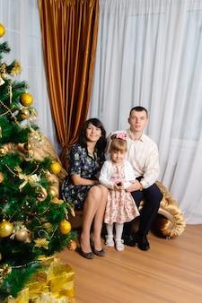 Мама, папа и дочка позирует с елкой