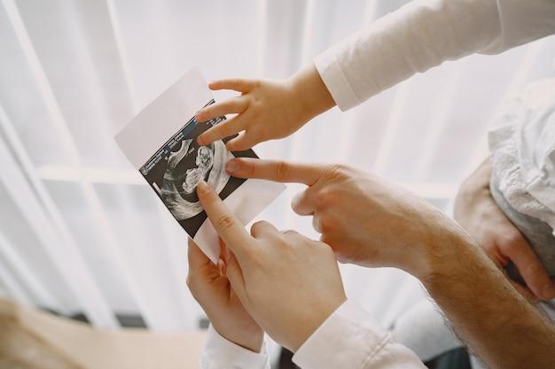 Мама, папа и дочь смотрят ультразвуковое изображение ребенка. семья в легкой одежде. семья ждет ребенка.