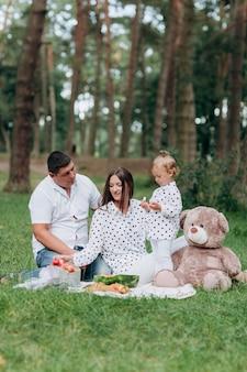 ママ、パパ、屋外の公園でテディベアとピクニックに小さな娘。夏休みのコンセプトです。母の日、父の日、赤ちゃんの日。自然に一緒に時間を過ごす家族。ファミリールック