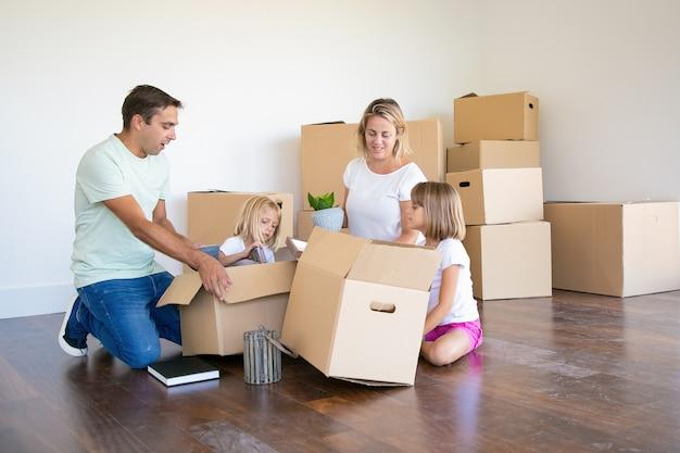 Мама, папа и маленькие дочери распаковывают вещи в новой квартире, сидят на полу и вынимают предметы из открытых ящиков