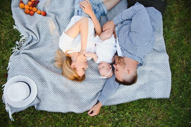 サマーパークの毛布の上に横たわっているママ、パパと幼い息子。夏休みのコンセプト。お母さん、お父さん、赤ちゃんの日。自然に一緒に時間を過ごす家族。ファミリールック