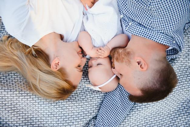 Мама, папа и маленький сын лежат на одеяле в летнем парке. концепция летнего отдыха. день матери, отца, ребенка. семья, проводящая время вместе на природе. семейный образ Premium Фотографии