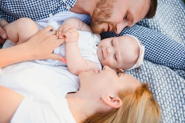 Мама, папа и маленький сын лежат на одеяле в летнем парке. концепция летнего отдыха. день матери, отца, ребенка. семья, проводящая время вместе на природе. семейный образ