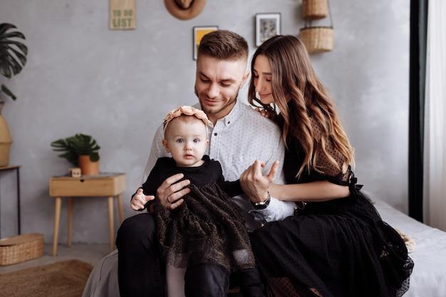 ママ、パパ、自宅でベッドの上を抱いて楽しんでいる小さな女性。母の日、父の日、赤ちゃんの日。屋内での幸せな家族の休日。家族の一見。一緒に時間を過ごす幸せな若い家族