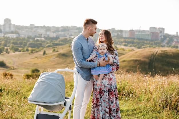 ママ、パパ、夏の日の屋外の芝生で楽しんでいる小さな女性。母の日、父の日、赤ちゃんの日。町の外でベビーカーと一緒に散歩に幸せな家族。
