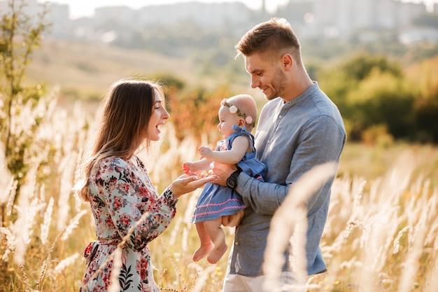 ママ、パパ、夏の日の屋外の芝生で楽しんでいる小さな女性。母の日、父の日、赤ちゃんの日。散歩に幸せな家族。