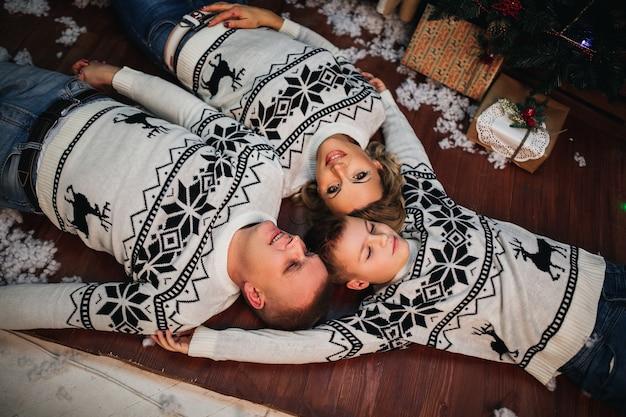 엄마 아빠와 아들은 바닥에 누워 똑같은 스웨터를 입은 카메라를보고 있습니다.